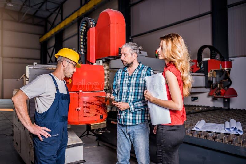 Coordenadores que verificam a instalação da máquina nova dos plasmas do CNC imagens de stock royalty free