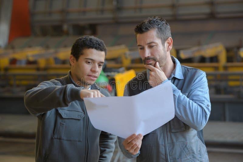 Coordenadores que verificam a máquina nova da instalação no salão industrial foto de stock