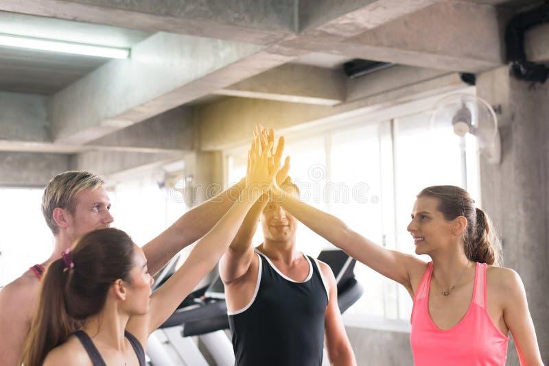 Coordinación de la mano de la gente del grupo motivada, del equipo amistoso joven deportivo atractivo y que se sostiene o unirse  imagen de archivo libre de regalías