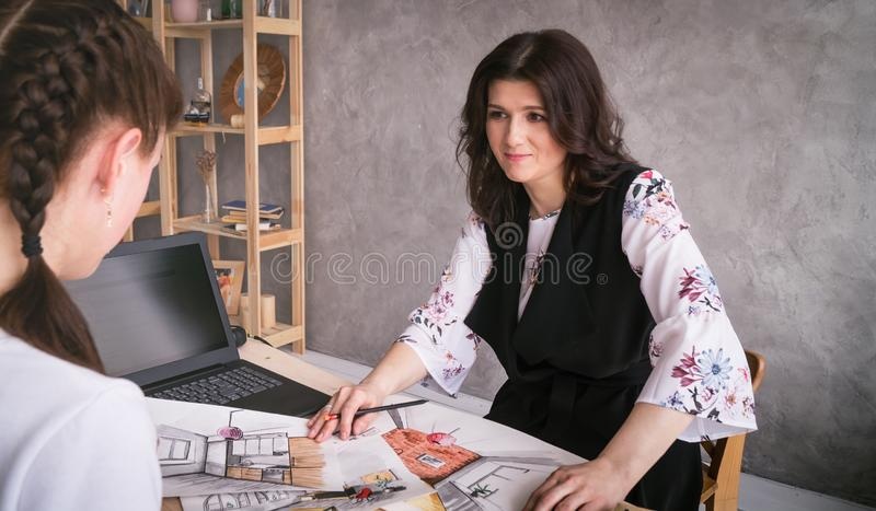 Coordination with the customer: A woman designer shows the customer samples of color on the plates and outline of the interiors royalty free stock photo