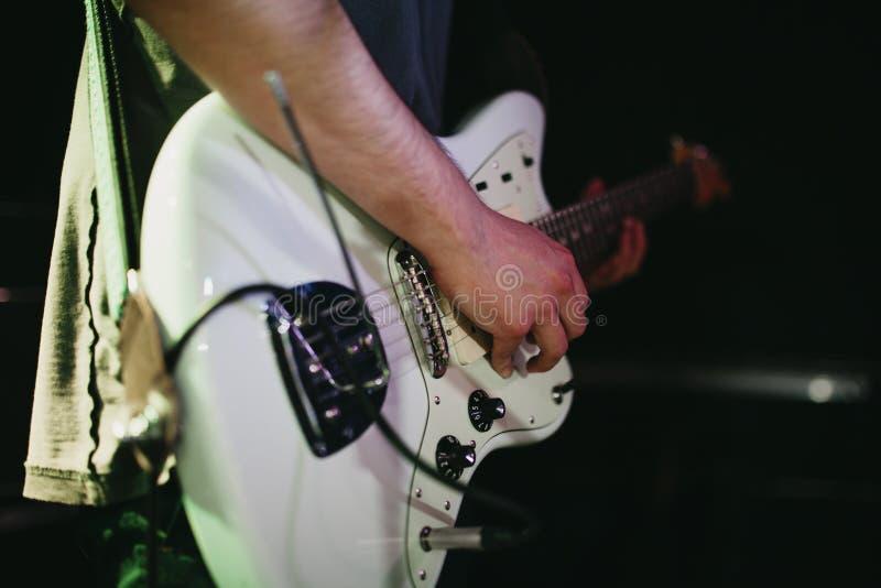 Coordonnée de l'homme jouant la guitare électrique blanche pendant un concert de rock indépendant photo libre de droits