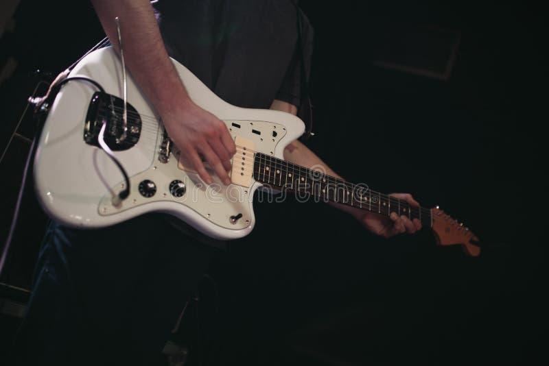Coordonnée de l'homme jouant la guitare électrique blanche pendant un concert de rock indépendant photos libres de droits