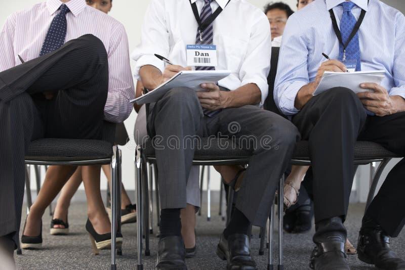 Coordonnée des délégués écoutant la présentation à la conférence image stock