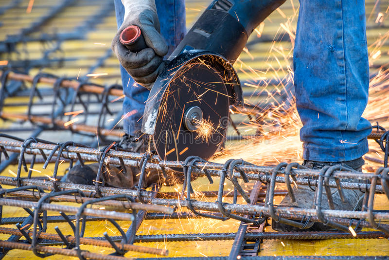 Coordonnées du travailleur d'ingénieur de construction coupant les barres d'acier et l'acier renforcé au chantier photographie stock