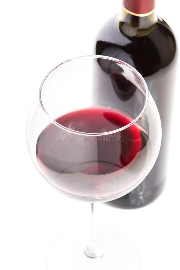 Copa con el vino rojo y la botella en el fondo blanco fotos de archivo libres de regalías
