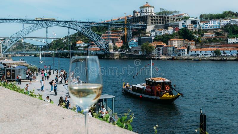 Copa de vino blanca que pasa por alto Cais DA Ribeira en el r?o el Duero en Oporto, Portugal fotos de archivo libres de regalías