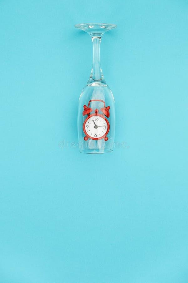 Copa de vino con el despertador rojo dentro en fondo azul con el espacio de la copia para el texto Tiempo creativo de la bebida d fotos de archivo libres de regalías