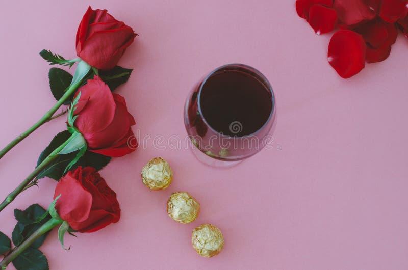 Copa de vino con las rosas rojas y los chocolates Día del `s de la tarjeta del día de San Valentín foto de archivo