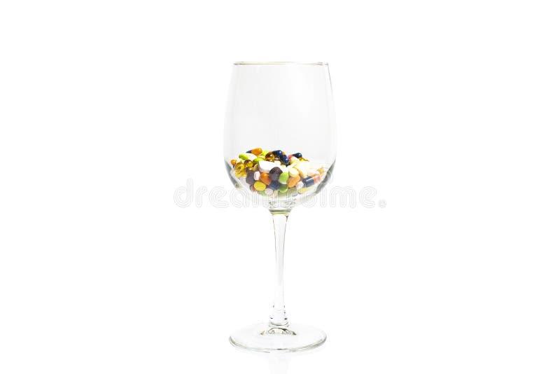 Copa de vino con muchas píldoras multicoloras, tabletas y cápsulas, aisladas en el fondo blanco con el espacio de la copia fotos de archivo