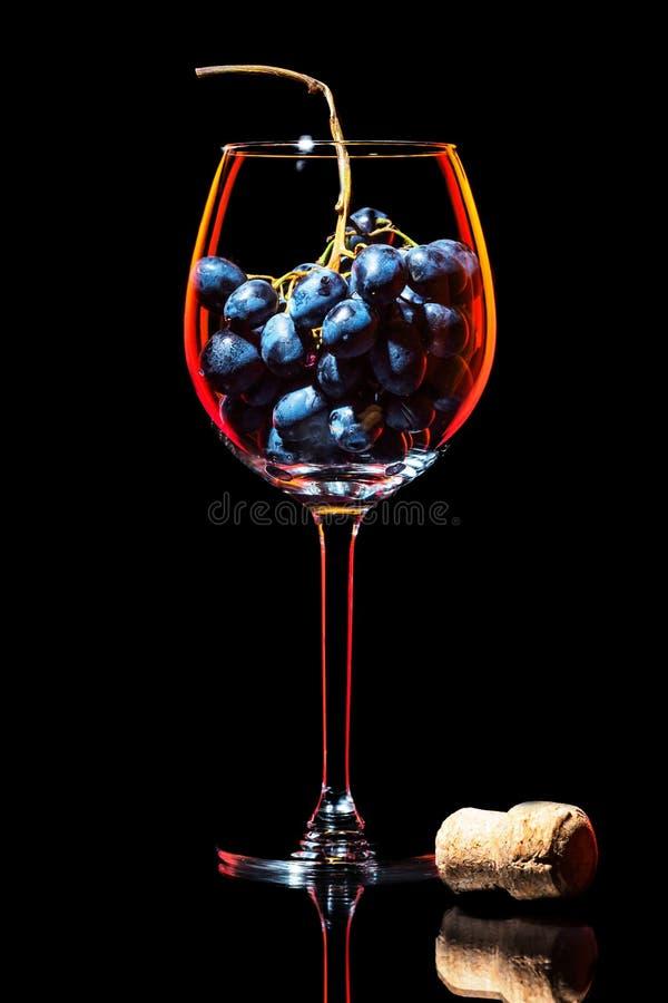 Copa de vino elegante de la silueta con el racimo de uvas rojas y de corcho tradicional fotos de archivo libres de regalías