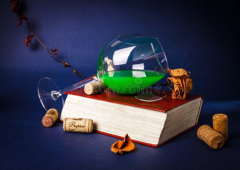 Copa de vino quebrada, una rosa y un libro en un oscuro fotografía de archivo libre de regalías