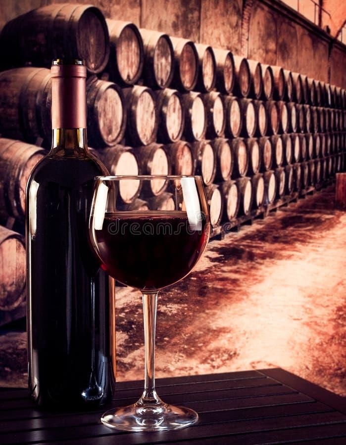 Copa de vino roja cerca de la botella en viejo fondo de la bodega imágenes de archivo libres de regalías