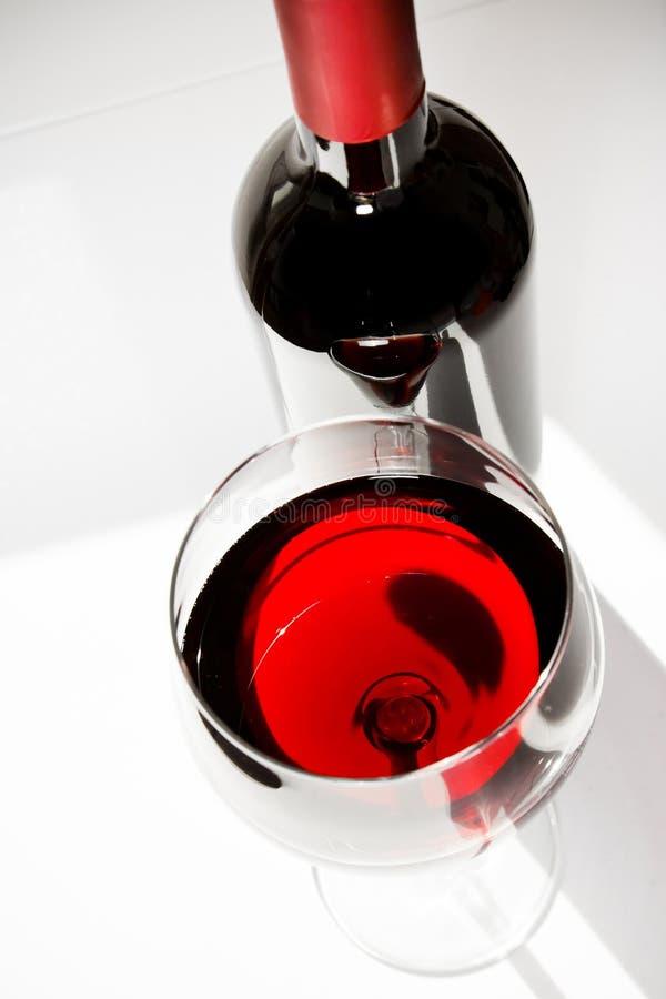 Copa de vino roja cerca de una botella bajo luz diaria fotografía de archivo libre de regalías