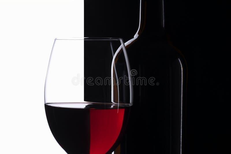 Copa de vino roja de la simetría elegante y una botella de vino imagenes de archivo