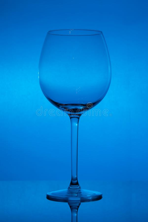 Copa de vino vacía en el fondo azul, copa vacía fotos de archivo