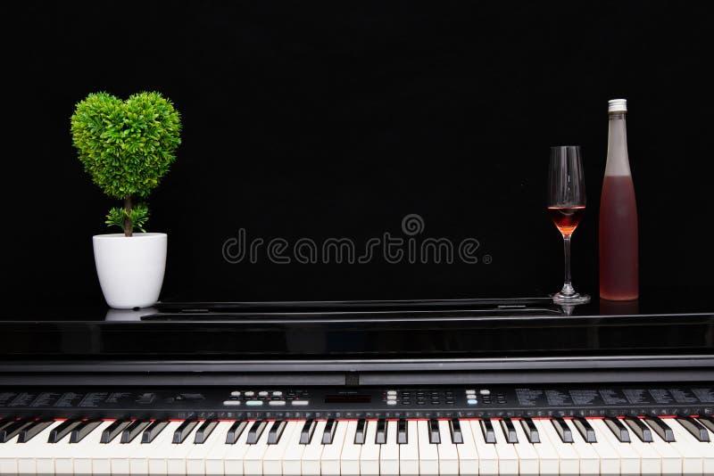 Copa de vino y botella en piano fotos de archivo libres de regalías