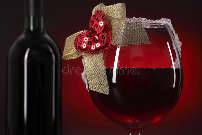 Copa de vino y botella rojas con el corazón fotos de archivo libres de regalías