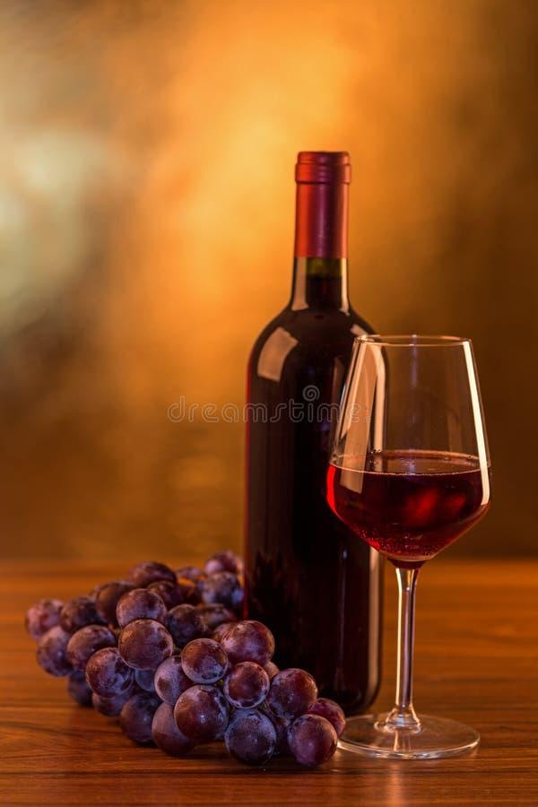 Copa de vino y botella rojas con las uvas en la tabla de madera y el fondo de oro imagen de archivo