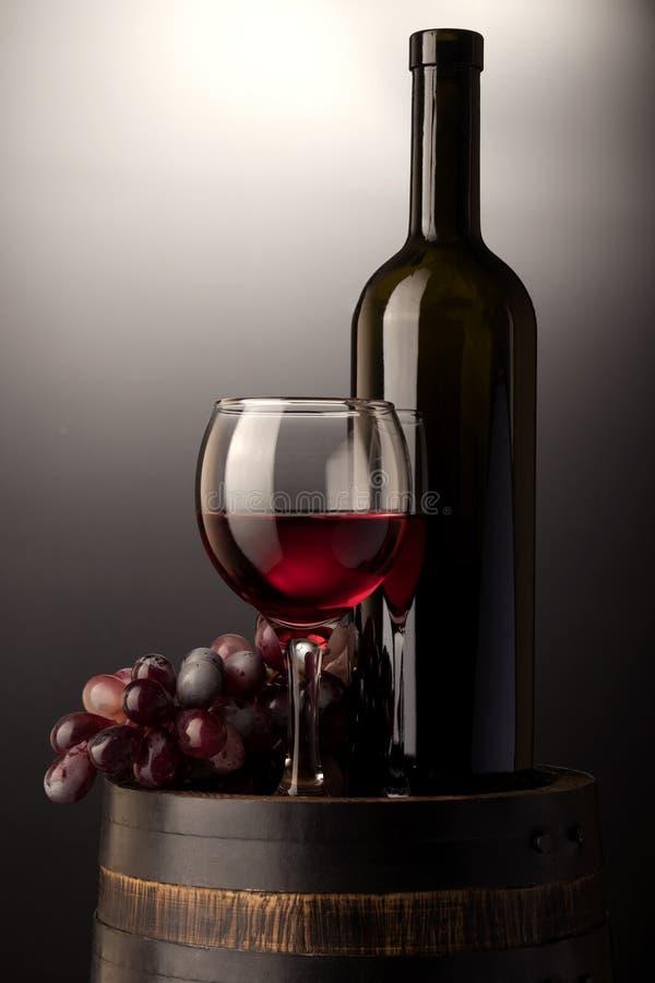Copa de vino y botella rojas en barril de madera imagen de archivo libre de regalías