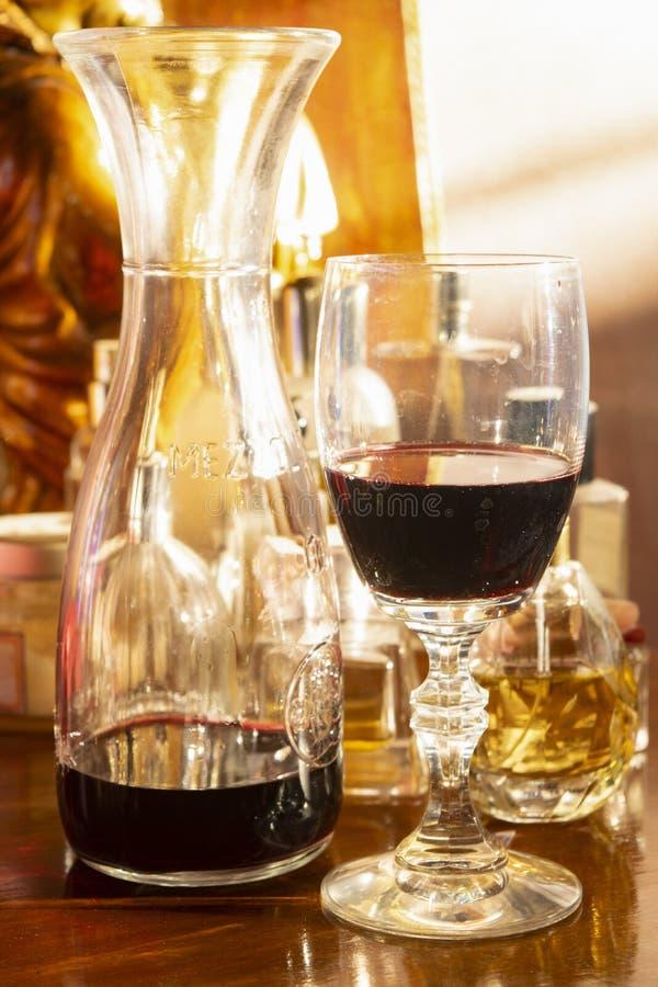 Copa roja con la jarra del vino imagen de archivo