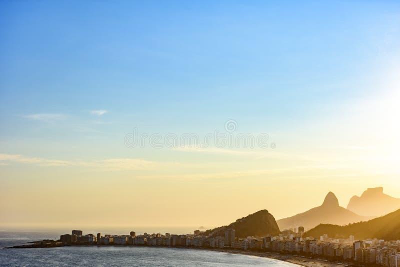 Copacabanastrand in Rio de Janeiro tijdens zonsondergang met zijn gebouwen en bergen royalty-vrije stock afbeelding