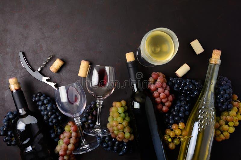 Copas con el vino blanco rojo y, las botellas, las uvas, el sacacorchos y los corchos mintiendo en fondo de madera oscuro fotografía de archivo