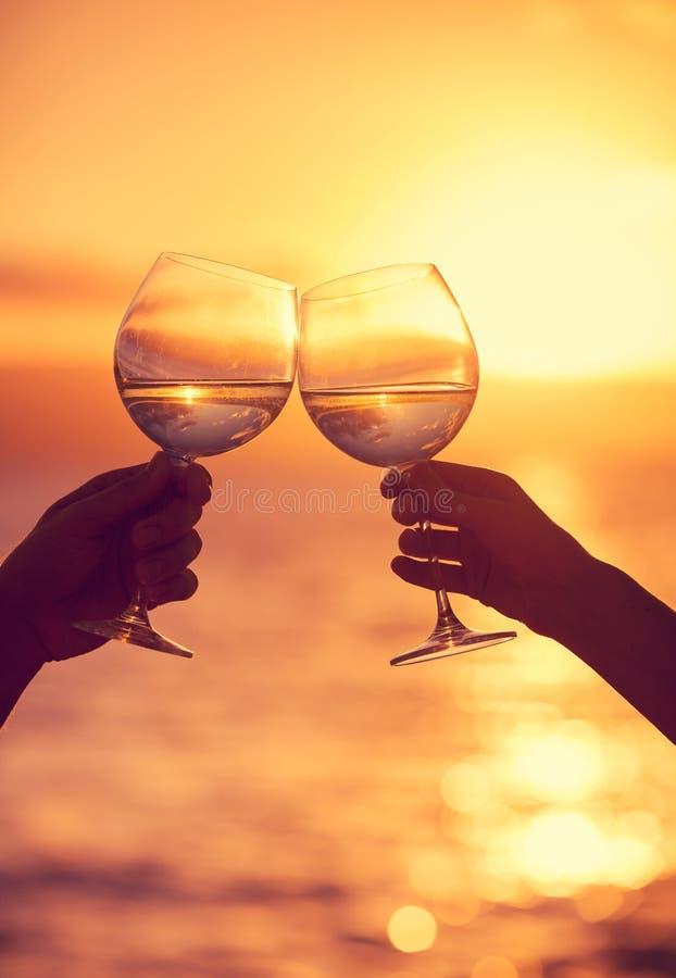 Copas de vino clanging del hombre y de la mujer con champán en la puesta del sol fotos de archivo libres de regalías