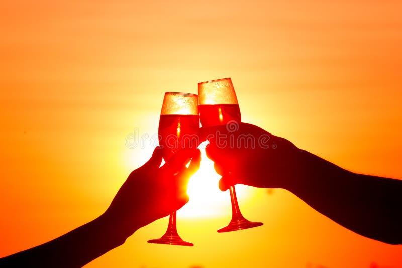 Copas de vino clanging del hombre y de la mujer con champán en la puesta del sol imagen de archivo libre de regalías