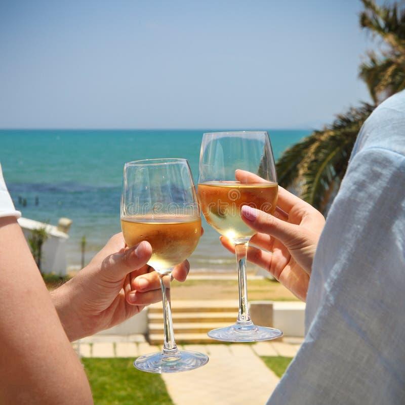 Copas de vino clanging del hombre y de la mujer con el vino blanco imagen de archivo libre de regalías