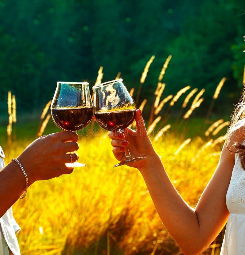 Copas de vino clanging del hombre y de la mujer en la puesta del sol fotografía de archivo