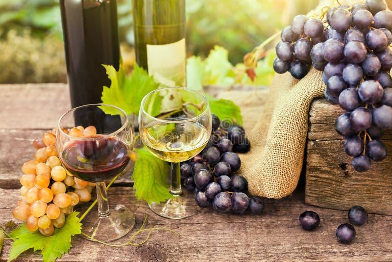 Copas de vino con el vino blanco rojo y fotos de archivo