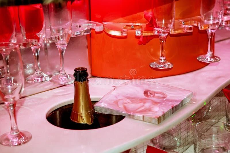 Copas de vino de la porción y una botella de champán en el coche en velas que llevan rojas Un marco horizontal fotos de archivo libres de regalías