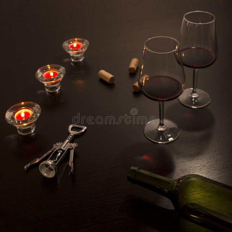 Copas de vino en una tabla con una botella vacía, un sacacorchos y los corchos de la botella en los tonos oscuros encendidos por  foto de archivo libre de regalías