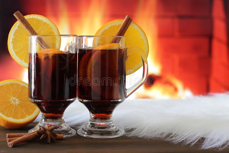 Copas de vino reflexionadas sobre delante de la chimenea ardiente fotografía de archivo