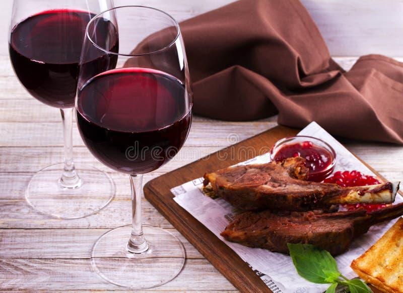 Copas de vino rojas Estante del cordero con la salsa y los verdes de la granada imágenes de archivo libres de regalías