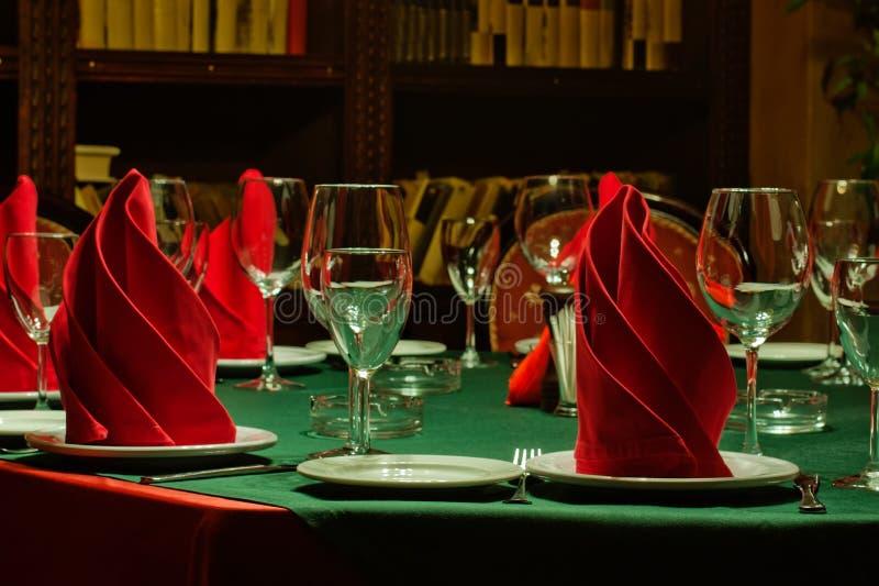 Copas de vino y placa servidas servicio de la tabla del restaurante Mantel verde, servilletas rojas, loza y cubiertos imágenes de archivo libres de regalías