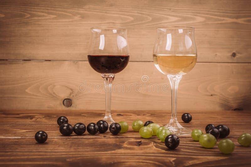 Copas de vino y uva rojas y blancas en la tabla de madera fotografía de archivo