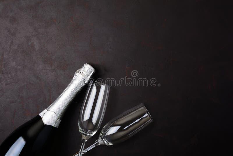 Copas y botella de champán con la mentira serpentina en fondo de madera negro Concepto de la celebración del Año Nuevo foto de archivo libre de regalías