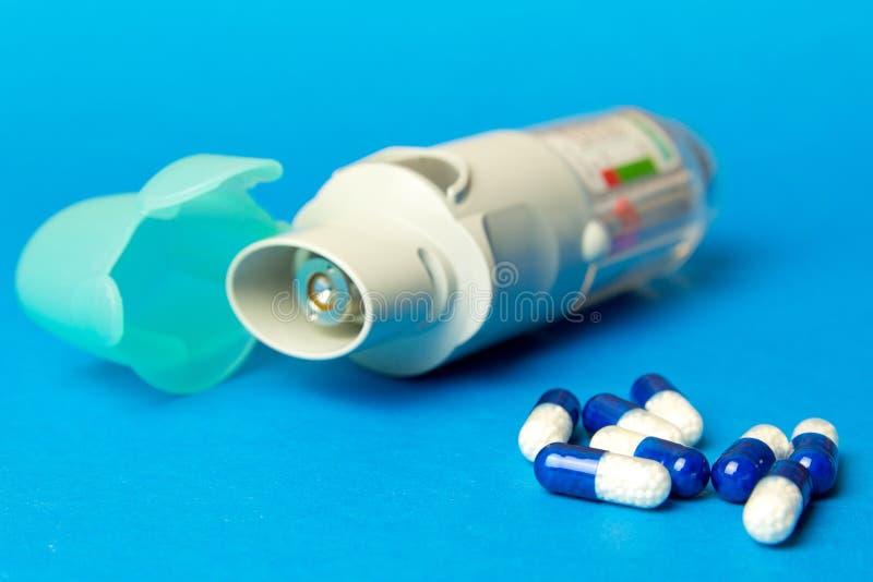 吸入器和药片反对哮喘在蓝色背景 Copd 免版税库存照片