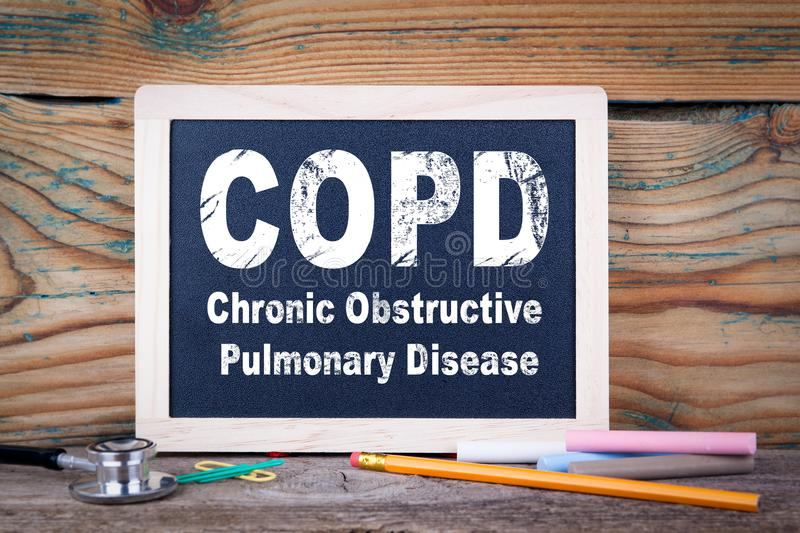 Copd, Chronic obstructive pulmonary disease. Chalkboard on a wooden background royalty free stock images