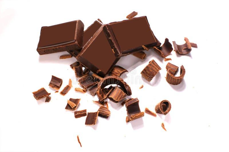 Copeaux et morceaux noirs délicieux de chocolat sur le fond blanc, vue supérieure photographie stock libre de droits
