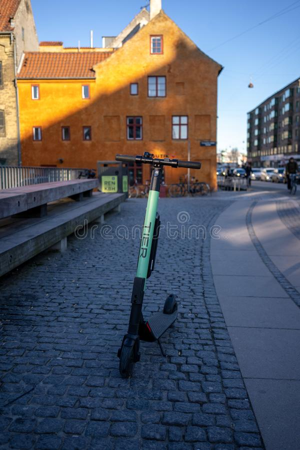 Copenhaga, Dinamarca - 1? de abril de 2019: 'trotinette' el?trico da s?rie em Copenhaga no sol da manh?, ao lado das casas ic?nic imagem de stock