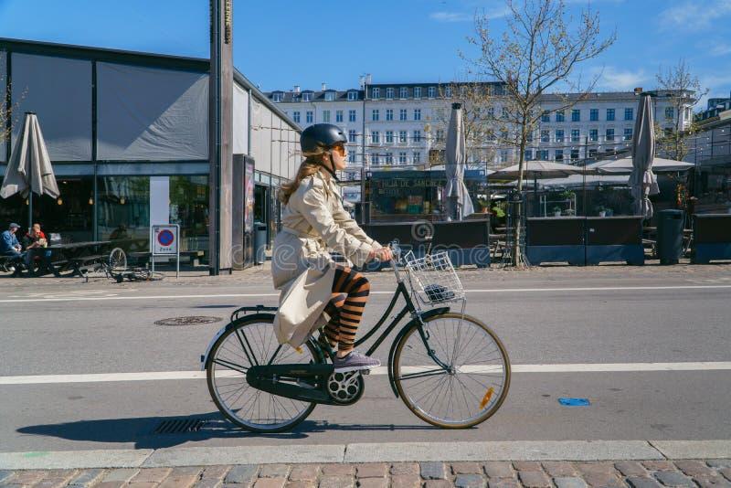 Copenhaga, Dinamarca - 6 de maio de 2018: Bicicleta da equitação da mulher na rua imagem de stock royalty free