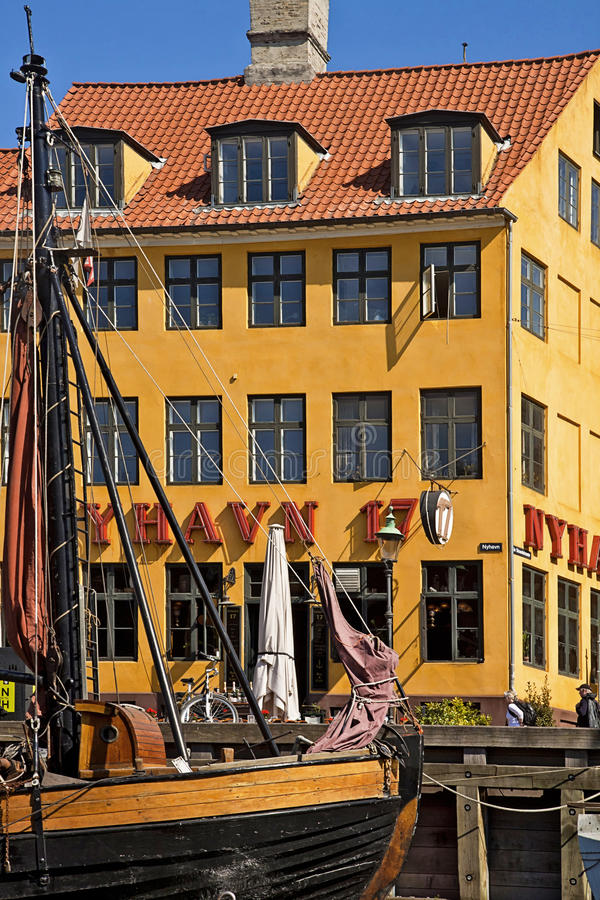 Copenhagen, antique house with bright facade and old ship moored in Nyhavn stock photo