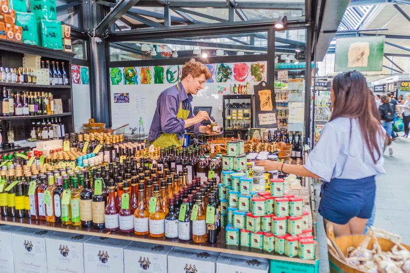 COPENHAGEN, DENMARK - AUGUST 28, 2016: People shop at a stall inTorvehallerne indoor food market in the centre of. Copenhagen royalty free stock photography