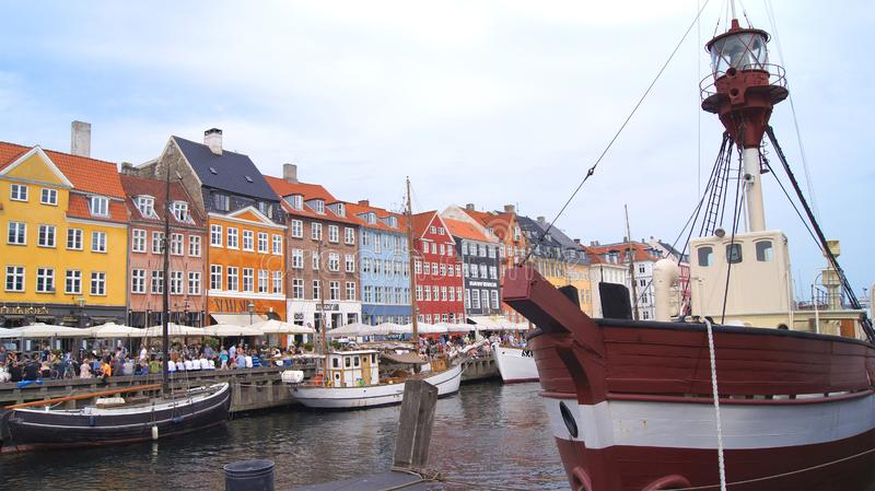COPENHAGEN, DENMARK - JUL 04th, 2015: Nyhavn district is one of the most famous landmark in Copenhagen during a summer. Day with ship in foreground royalty free stock photography
