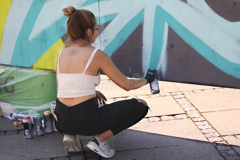 Female street artist painting colorful graffiti on wall - Modern art concept with urban girl painting live murales with aerosol co stock image