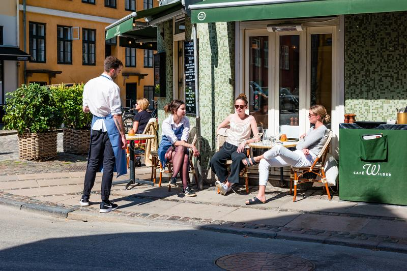 Street life in Copenhagen. People relaxing in a street cafe royalty free stock image