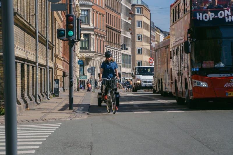 Copenhagen,Denmark - May 6, 2018: Woman riding bicycle on the street. stock photos