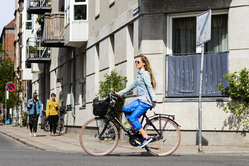 Woman riding bicycle showing left turn signal. Street style royalty free stock image